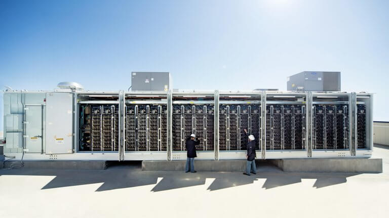 people in front of large solar batteries